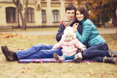 Happy loving family(mother, father and little daughter kid) outd. Oors walking having fun on a park in autumn season. Fallen yellow leaves on a background. Cold Stock Images