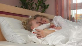 Happy loving family. Mother and her daughter child girl play and hug in bed stock video