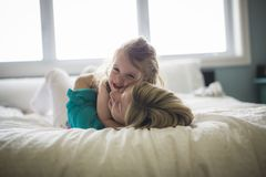 Happy loving family. Mother and her daughter child girl playing and hugging.on bed Stock Photos