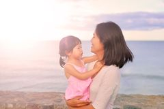 Happy loving family. Mother and her daughter child girl playing and hugging on sea background in the evenin stock photo