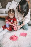 Happy loving family. Mother and her daughter girl play tea-party and drink tea from cups in children room. Funny mom and royalty free stock image