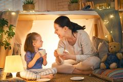 Happy loving family. Mother and her daughter girl play tea-party and drink tea from cups in children room. Funny mom and lovely child having fun indoors royalty free stock images