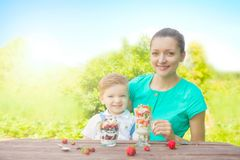 Happy loving family. Mother and her son child boy are eating laered dessert in sunny day in green garden Stock Photography