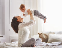 Happy loving family. Mother playing with her baby in the bedroom royalty free stock images