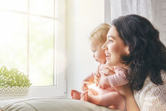 Happy loving family. Mother playing with her baby in the living room stock photo