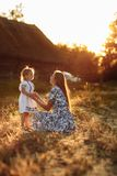 Happy family. Emotional and cheerful young mother with her little laughing daughter watching the rainbow sitting royalty free stock image