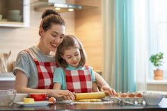 Happy family in the kitchen. Happy loving family are preparing bakery together. Mother and child daughter girl are cooking cookies and having fun in the kitchen royalty free stock photos