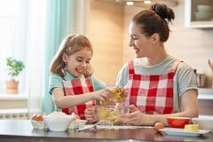 Happy family in the kitchen. Happy loving family are preparing bakery together. Mother and child daughter girl are cooking cookies and having fun in the kitchen royalty free stock photography