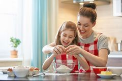 Happy family in the kitchen. Happy loving family are preparing bakery together. Mother and child daughter girl are cooking cookies and having fun in the kitchen stock images