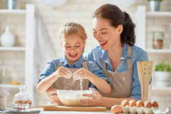 Homemade food and little helper. Happy loving family are preparing bakery together. Mother and child daughter girl are cooking cookies and having fun in the royalty free stock images