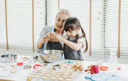 Happy loving family are preparing bakery together. Mother and her daughter child girl are cracking an egg into a bowl, bake. Cookies in the kitchen.Homemade stock photo