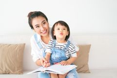Happy loving family. Pretty young asian mother reading a book to. Her daughter royalty free stock photo
