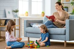 Happy loving family. Pretty young mother is reading a book and her daughters are playing royalty free stock image