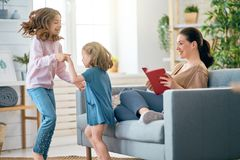 Happy loving family. Pretty young mother is reading a book and her daughters are playing stock photo