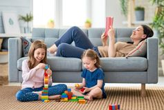 Happy loving family. Pretty young mother is reading a book and her daughters are playing stock photography