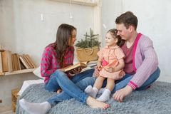 Happy loving family. pretty young mother reading a book to her daughter stock image
