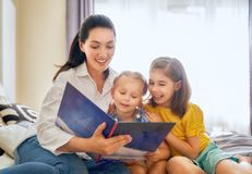 Mom and children reading a book Royalty Free Stock Images