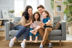Happy loving family. Young mother, father and their daughters girls playing at home. Funny mom, dad and lovely children are having fun with tablet royalty free stock photos