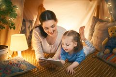 Happy loving family. Young mother and her daughter girl play in children room at the bedtime. Funny mom and lovely child are having fun with tablet stock image