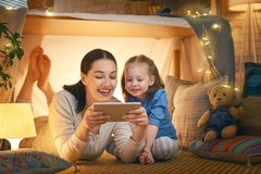 Happy loving family. Young mother and her daughter girl play in children room at the bedtime. Funny mom and lovely child are having fun with tablet royalty free stock images