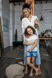 Happy loving family. Young mother and her daughter girl play in kids room. Funny mom and lovely child are having fun with tablet stock photography