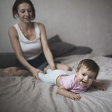 Happy loving family. young mother playing with her baby in the b Stock Photos