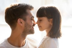 Happy loving father and kid daughter touching noses enjoy tenderness. Happy loving father and cute kid daughter touching noses enjoy moment of tenderness care royalty free stock image