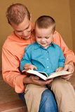 Happy loving father reading with his son. Happy loving father smiling and hugging his son Royalty Free Stock Photo