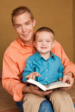 Happy loving father reading with his son. Happy loving father smiling and hugging his son Stock Photography
