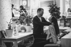Happy loving guy puts his hands at the girl`s shoulders sitting at the table in the cafe and looks at her. Black and stock image