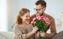 Happy loving   couple. husband gives his wife flowers at home royalty free stock photo