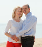 Happy loving mature couple against sea Stock Image