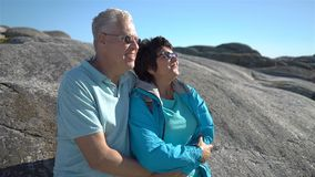 A happy loving mature couple enjoys a walk among the coastal stones on the seashore. They hold hands, admire the scenery, hug and kiss. Slow motion stock video footage