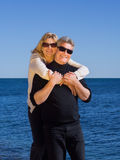 Happy loving middle-aged couple on beach. Happy loving middle-aged couple standing at the beach in the hot summer sun in their sunglasses and smart casual Royalty Free Stock Image