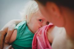 Happy loving mother breastfeeding little baby daughter. Happy loving mother breastfeeding cute little baby daughter royalty free stock photos