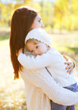 Happy loving mother hugging child in autumn day royalty free stock photo