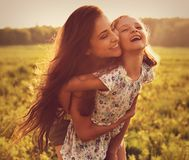 Happy loving mother hugging her laughing kid girl on sunset brig Royalty Free Stock Photo