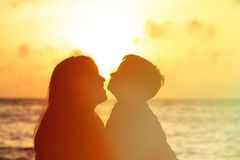 Happy loving mother and son at sunset beach Royalty Free Stock Photos