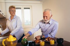 Loving senior couple having fun preparing healthy food on breakfast in the kitchen stock images