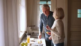 Happy loving senior mature couple having fun preparing healthy breakfast