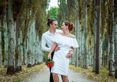 Happy loving wedding couple in the autumn park. Young handsome  groom embracing  his beautiful smiling bride in white dress, holding bouquet of red roses Royalty Free Stock Photo
