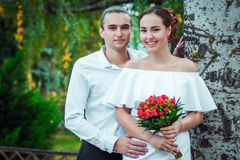 Happy loving wedding couple in the autumn park. Young handsome  groom embracing  his beautiful smiling bride in white dress, holding bouquet of red roses Stock Photography