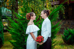 Happy loving wedding couple standing in the autumn park. Royalty Free Stock Images