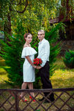 Happy loving wedding couple standing in the autumn park. Royalty Free Stock Photography