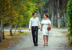 Happy loving wedding couple walking in the autumn park. Young handsome smiling  groom holding hand of his beautiful laughing bride in white dress, holding Stock Photography