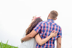 Happy loving young adult couple spending time on the field on sunny day. Happy young adult couple in love spending time on the field on sunny day outdoors royalty free stock photo