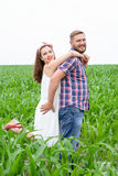 Happy loving young adult couple spending time on the field on sunny day. Happy young adult couple in love spending time on the field on sunny day outdoors royalty free stock photography