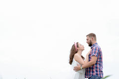 Happy loving young adult couple spending time on the field on sunny day Stock Photography