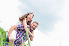 Happy loving young adult couple spending time on the field on sunny day. Happy young adult couple in love spending time on the field on sunny day outdoors stock image