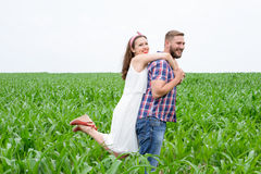 Happy loving young adult couple spending time on the field on sunny day Stock Image